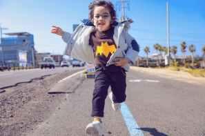 boy in eyeglasses running on the road