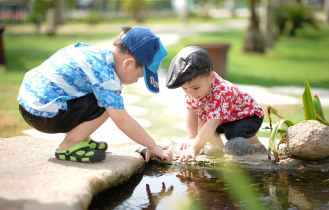 boy in blue and white shirt playing near on body of water with boy in red shirt