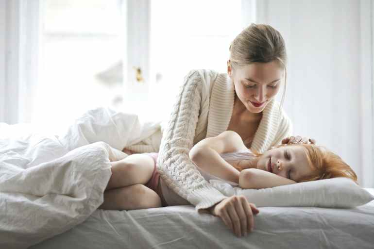 mother and child resting on bed