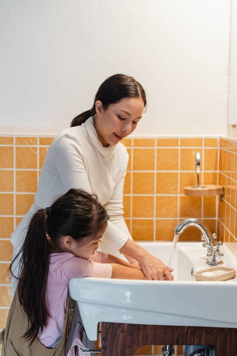 mom teaching little daughter to wash hands properly