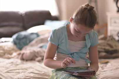 girl sitting on bed holding tablet computer